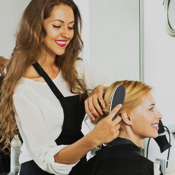 Femme qui se fait brosser les cheveux chez un coiffeur