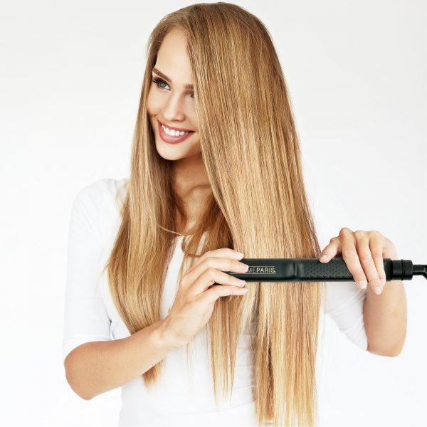 Femme qui se lisse les cheveux avec le lisseur Ana