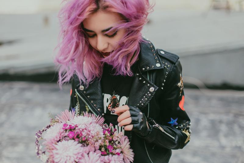 Femme aux cheveux rose qui tient un bouquet de fleurs
