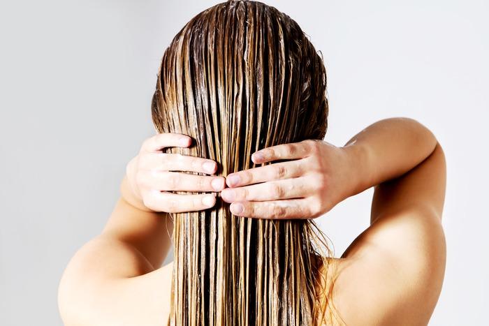 femme qui s'applique de l'après-shampoing