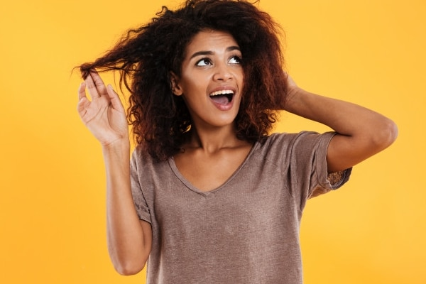Jeune femme en train de toucher ses cheveux bouclés