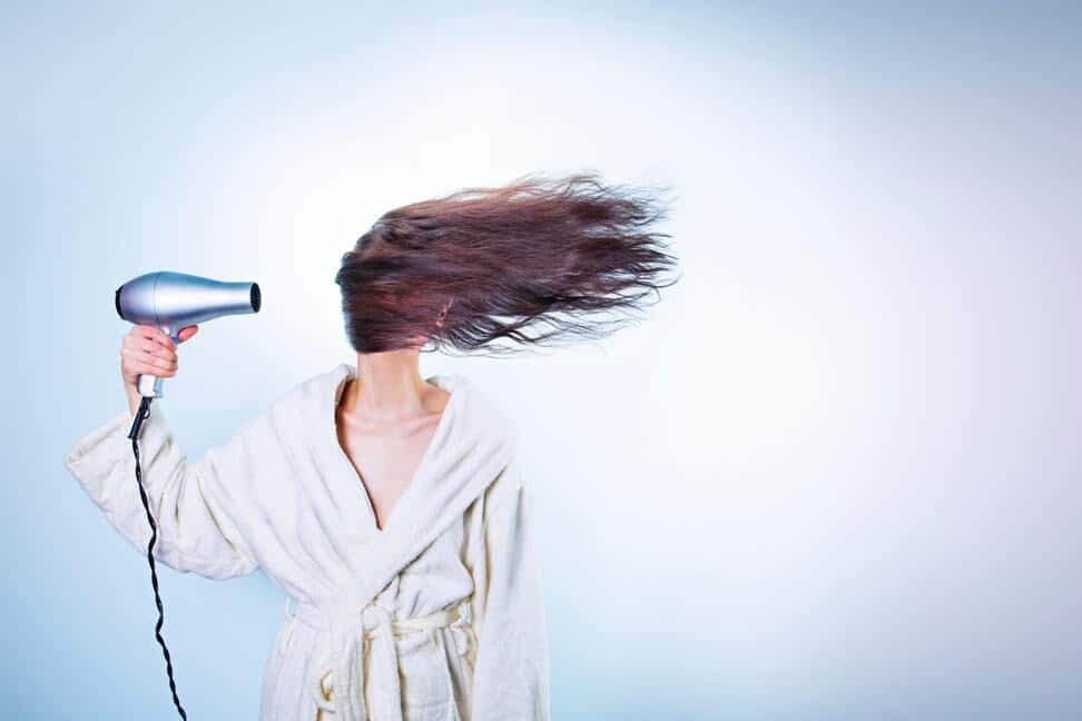 Jeune femme utilisant un appareil chauffant